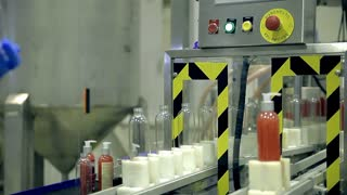 Automatic conveyor line driven by motors. Plastic bottles with dispensers are moving on the line. The line produces shower gels, liquid soaps, shampoos and other means of personal hygiene