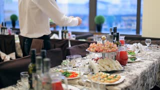 Before the beginning of the holiday a young waiter is carrying ready-made meals to the tables with a huge amount of food