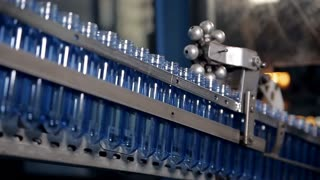 Blanks for water bottles are moving on the production line. They are being pushed by automated robots