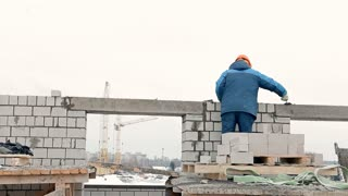 Builders are constructing a brick block of flats in a cold winter. They are stacking bricks, using cement, spatulas