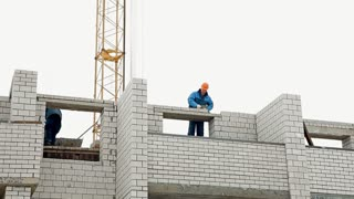 Builders are constructing a multi-storey brick house in a cold winter. They are stacking bricks. A high crane is in the background
