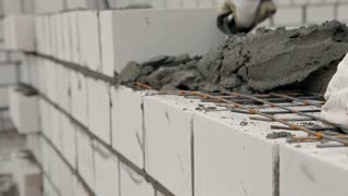 Builders are constructing a multi-storey brick house in a cold winter. They are stacking bricks, using cement, spatulas