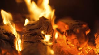 Firewood is lying in the fireplace. Fire is burning with beautiful spurts of flame. Close-up shot, zoom out