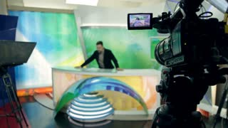 In a small news studio a presenter is rehearsing in front of cameras