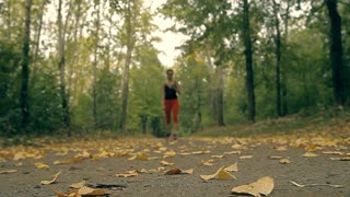 In autumn a woman decided to run to burn her fat. She is switching on her music player and starting to move down the alley between fallen leaves