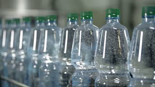 Plastic bottles with aerated mineral water are moving along the conveyor. There are bubbles in bottles