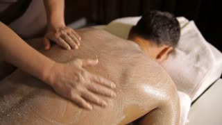 Professional massage therapist is applying special scrub on a client's back with his hands and spreading it. Close-up shot