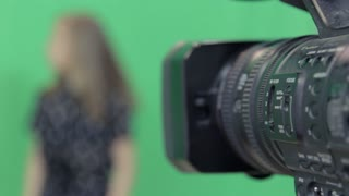 The camera is looking at the girl in the glasses. She is talking something on a green background