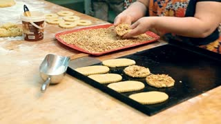 The chef is putting rings of pastry topped with peanuts on a baking sheet to send it into the oven