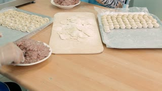 The cook is putting meat into the dough and wrapping it. Next he's going to boil the dumplings