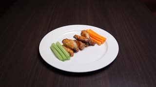 There is a beautiful white plate on a dark wooden table. The plate is full of elegant meals, which are perfect as a snack to beer