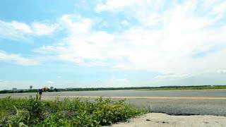 A airplane is landing on the airstrip in a bright day.