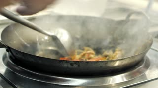 A chef is cooking Chinese Udon noodles with vegetables