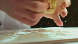 A chef is kneading dough for cakes
