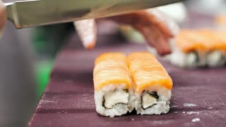A chef is making Philadelphia rolls