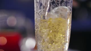 A festive glass is being filled with champagne
