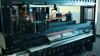 A machine is cutting red fabric