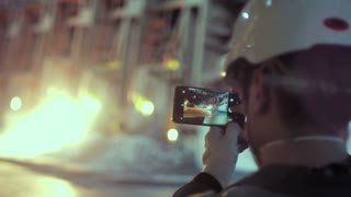 A metallurgist is shooting on the phone the process of melting metal