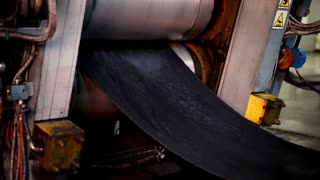 A press with rotating shafts is giving rubber for tyres