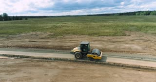 A road roller is compacting a fresh paved road