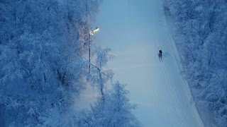 A skier is moving on a night ski run