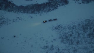 A snowmobile is dragging two cart-sleds