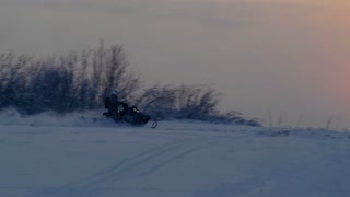 A snowmobile is riding in the Arctic at sunset