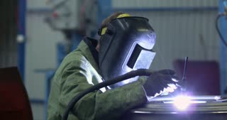 A welder in a mask and overalls at work