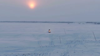 Aerial. A snowmobile ride at sunset