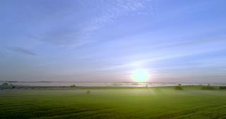 The sun is illuminating a green field with rays.