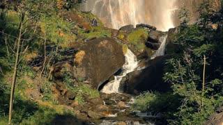 Waterfall in Europe. Water is flowing on green rocks.
