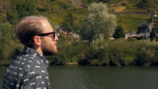 Young bearded hipster in sunglasses is sailing on a ship. The river is in Europe, there are beautiful buildings in the background