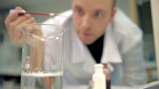 Young laboratorian in a white coat is adding an ingredient into personal care means with eyedropper. The liquid is painted in red. It could be shower gel, liquid soap, shampoo, etc. There is a clear