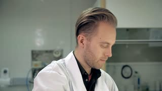 Young laboratorian in a white coat is mixing the ingredients in a personal care means. It could be shower gel, liquid soap, shampoo, etc. The man is very focused. Liquid sequins are in a measuring