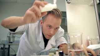 Young laboratorian in a white coat is mixing the ingredients in a personal care means. It could be shower gel, liquid soap, shampoo, etc. There is a clear liquid in a measuring glass