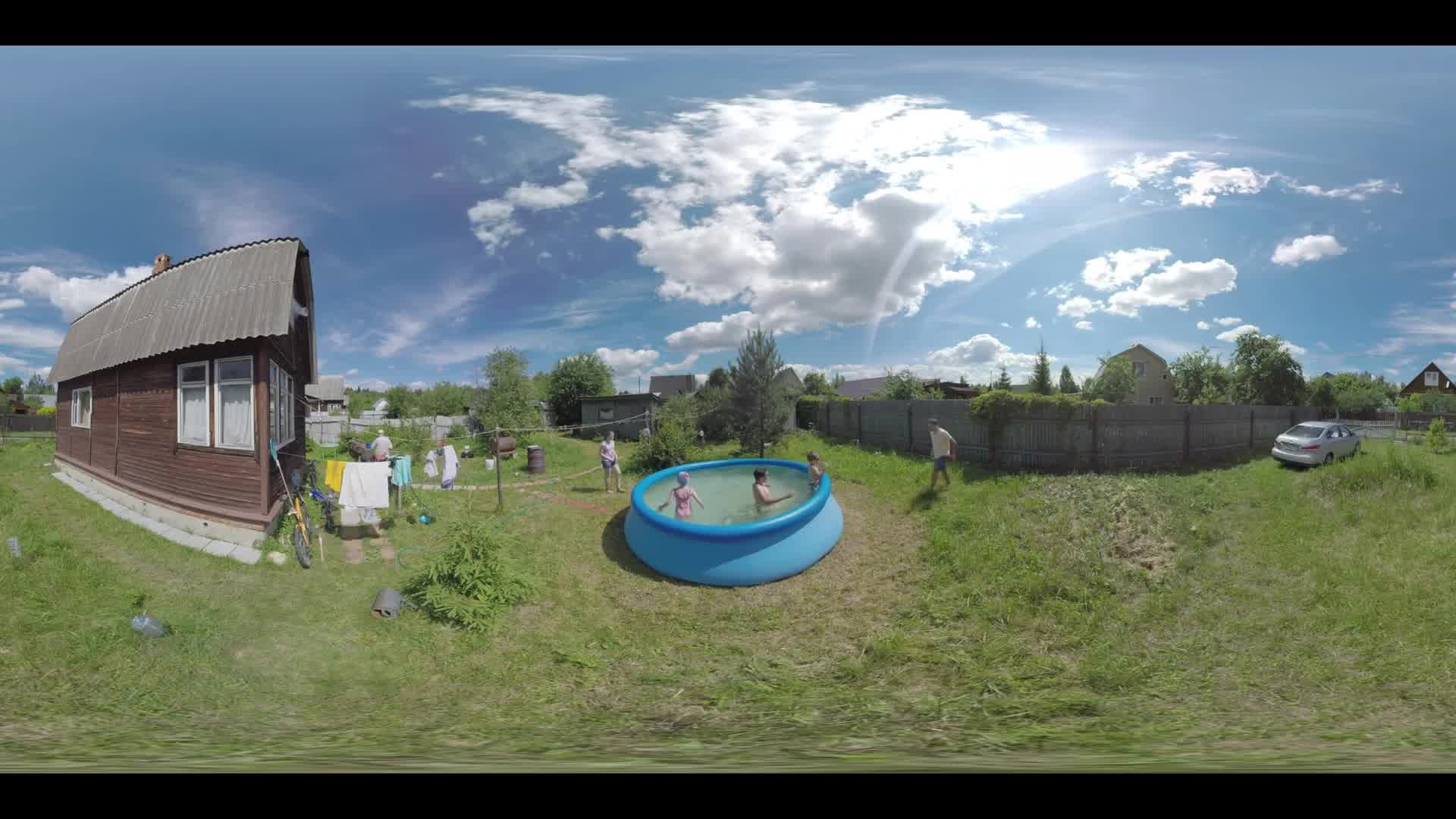 360 VR video. Two boys and a girl having fun in outdoor rubber pool during the rest in the countryside. Summer weekend in the country house. Adults watching kids. Ruza, Moscow region. Real sound included