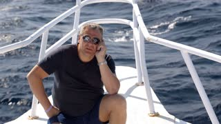 50 years old man sitting on the bow of sailing yacht and talking on the phone