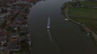 Aerial - Dutch town scene in the evening with river and sailing barge