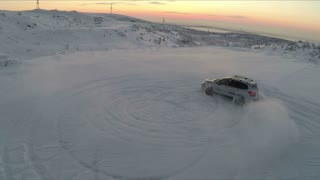 Aerial shot of a car drifting on snowfield making circles with view to the distant snow covered hills and evening sky. Beautiful northern nature