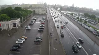 Aerial shot of car traffic on Krymsky Bridge, parking lots and people walking on sidewalk on nasty rainy day in Moscow, Russia