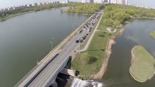 Aerial shot of cars driving along the narrow riverside road and crossing green plantings in the city