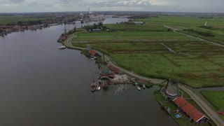 Aerial shot of Dutch village with view to the river, old windmills and green fields