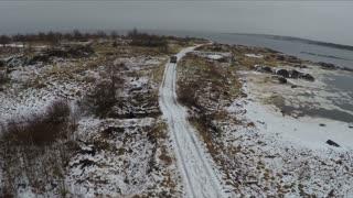 Aerial shot of minivan driving along the narrow road along the waterside. Visiting Rabocheostrovsk, township near Solovki