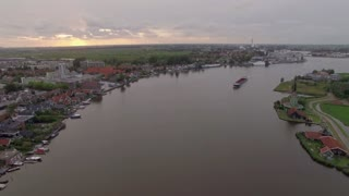 Aerial shot of ship sailing along the river flowing through the township in Netherlands. View at sunset