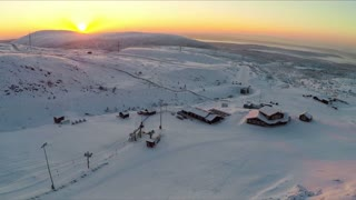 Aerial shot of ski resort. View to the area with wooden buildings and ski-lifts. Evening sky in light of golden sunset. Scene with snowfields and hills. Khibins, Russia