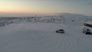 Aerial shot of skilled driver making circles on the snow while drifting. Winter nature and evening sky scene