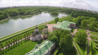 Aerial shot of Tsaritsyno park in Moscow. View to the ancient architecture among green lawns and trees and big pond. Popular place to visit