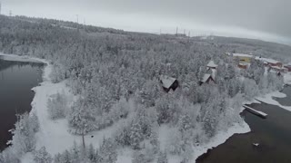 Aerial shot of winter camp located in pine wood in Finland. Snowy landscape with lakes