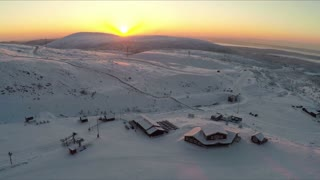 Aerial shot of winter ski resort. Snowy area with wooden buildings, golden sun going down behind the mountains. Khibins, Russia