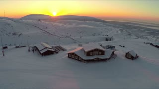 Aerial shot of wooden houses in snowfields. Ski centre on the north. Winter scene with hills and golden sunset